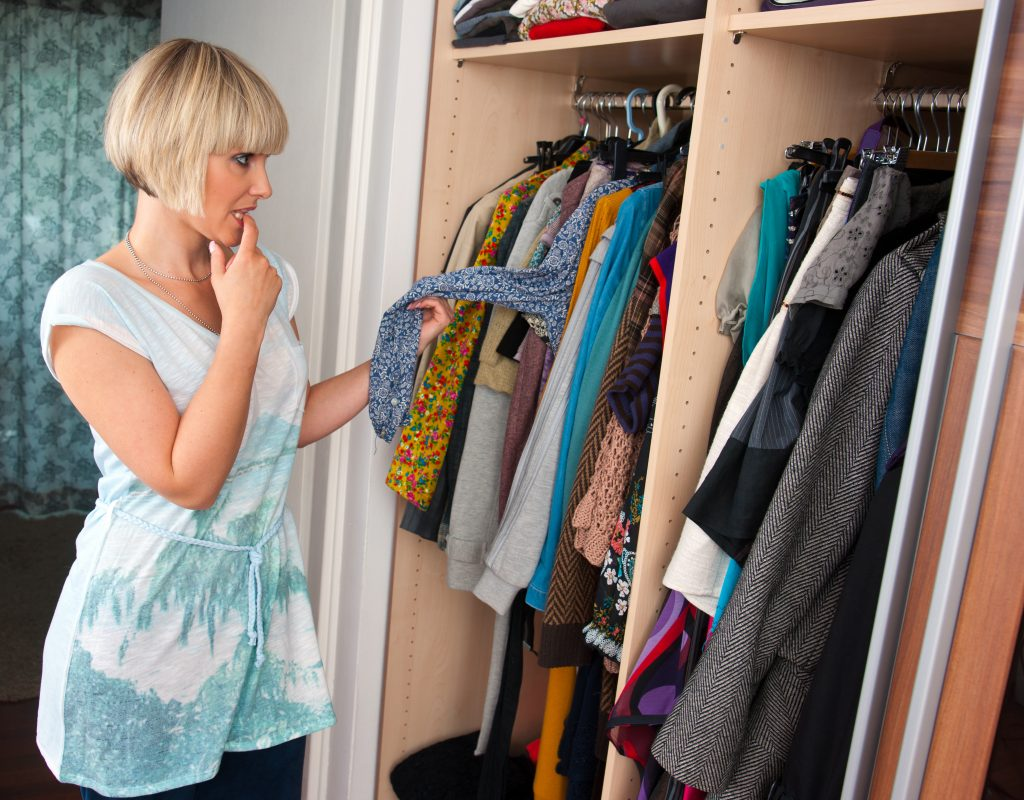 woman sorting fall clothing in her closet
