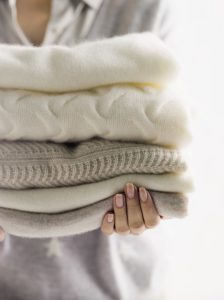 woman holding some cashmere sweaters